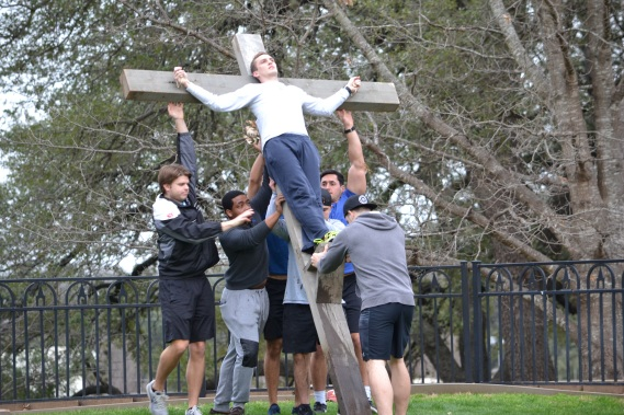 senior Aaron Midkiff, who normally portrays Pontius Pilate in the Easter Pageant, stands in for a thief as actors practice lifting a man's weight on the cross during rehearsal at Luther Memorial on Thursday, Feb. 28. Seen pushing the cross up left to right are: junior Ethan Grill, junior David Taylor, freshman Jaden Napolez, senior Matt McVey, and senior Glen Fontenelle. Photos by Madeline Oden/ The Bells